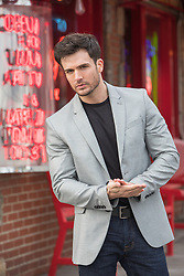 chiseled good looking man in a blazer and black tee shirt by a cafe
