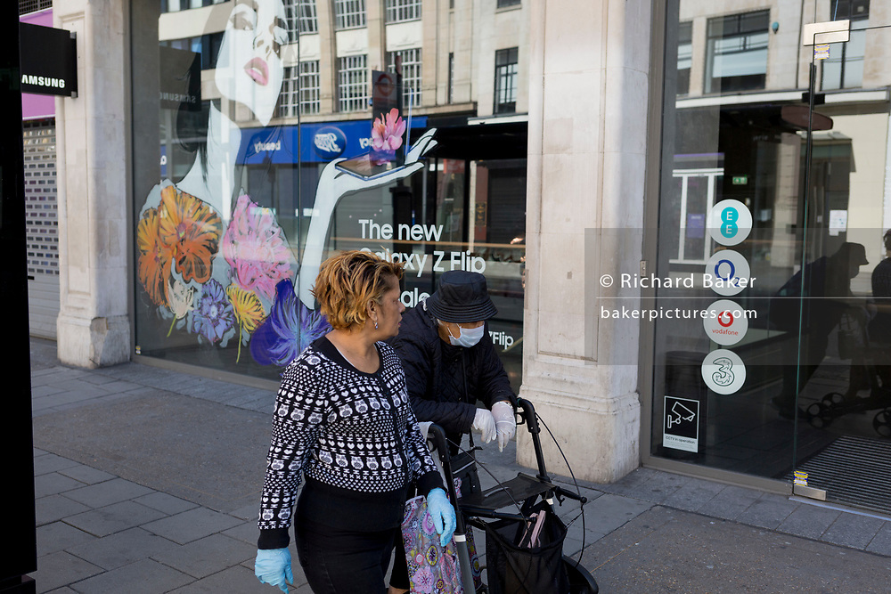 At the beginning of the fourth week of the UK government's lockdown during the Coronavirus pandemic, and with 120,067 UK reported cases with 16,060 deaths, two women wearing masks walk past a Samsung phone retailer on Oxford Street that would normally be a busy thoroughfare for shoppers and traffic and wich remains otherwise quiet at mid-day, on 20th April 2020, in London, England.
