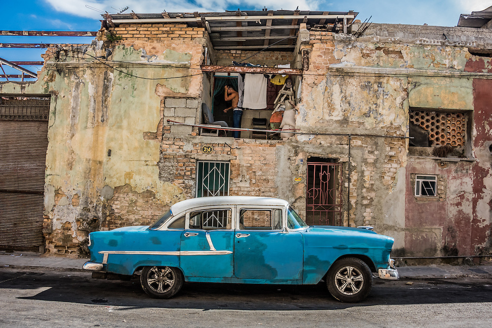 A man gets ready for the day in a room open to the street in Havana, Cuba. A vintage car sits in front of the crumbling building.