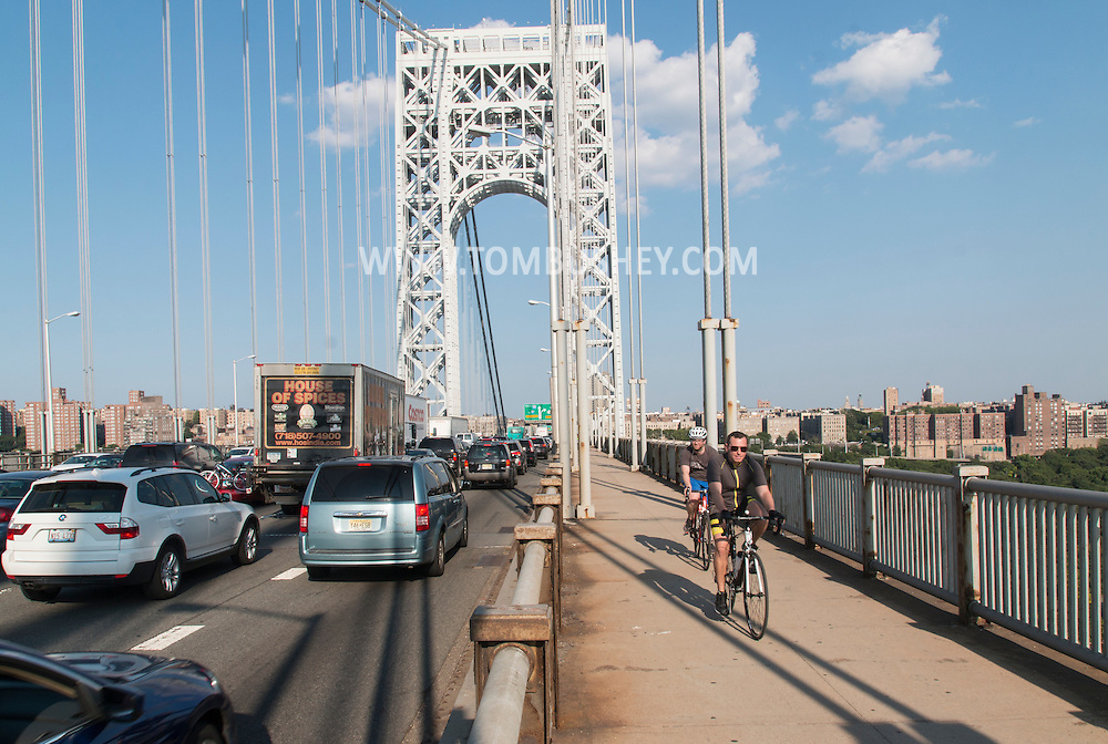 New York, New York - Cars and trucks head into Manhattan on the George Washington Bridge as two bicyclists ride toward New Jersey on July 11, 2015.