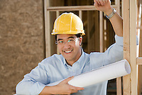 Man holding rolled up blueprint in construction site