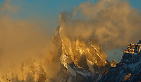 It is that moment when the mountains emerge from the clouds that are the most special, when nature can be at its most powerful. Patagonia's Mount Cerro Torre, the dark serrated wonder, at the very moment  it emerges from the clouds, blown by gale force winds, and dressed  in the warm light of the morning sun.