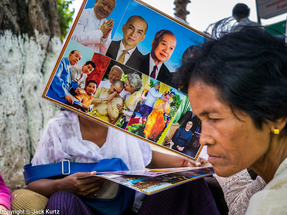 02 FEBRUARY 2013 - PHNOM PENH, CAMBODIA:  A woman holds pictures of late King Norodom Sihanouk during the mourning period for Sihanouk, who ruled Cambodia from independence in 1953 until he was overthrown by a military coup in 1970. Sihanouk died in Beijing, China, in October 2012.     PHOTO BY JACK KURTZ