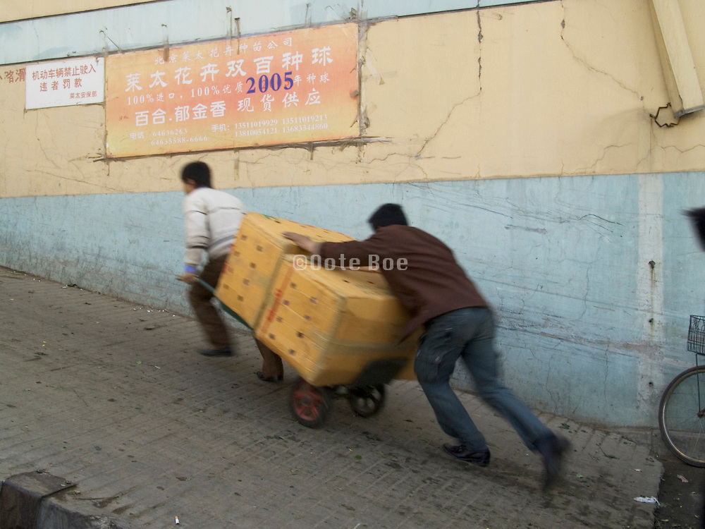 two man pushing an heavy load up a ramp China