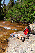 A teenage backpacker takes a break at Mono Creek; John Muir Wilderness, Sierra National Forest, Sierra Nevada Mountains, California, USA.