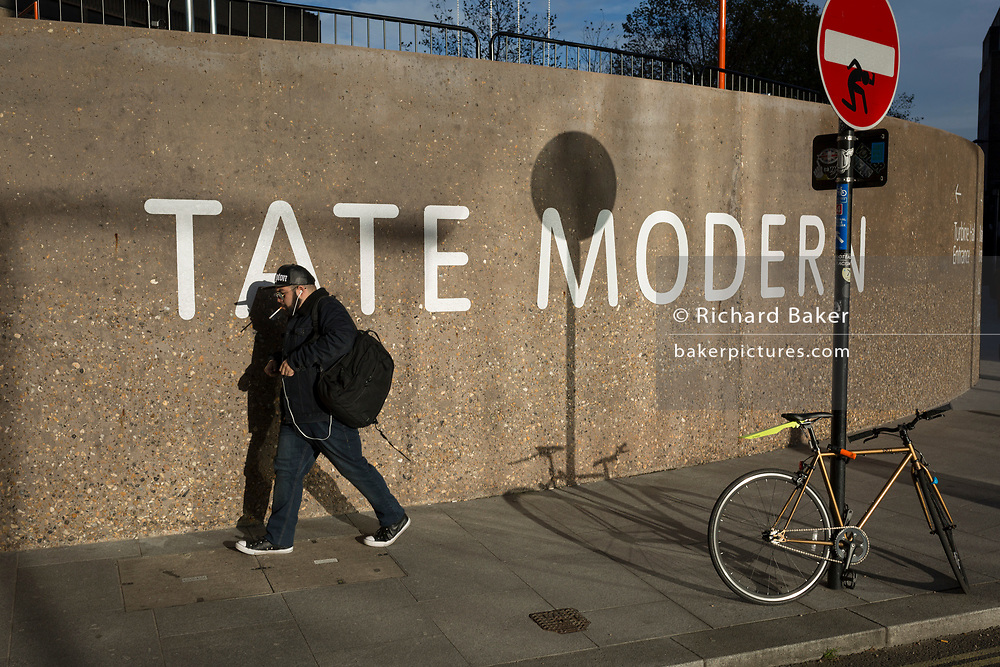 A smoker walks past the Tate Modern art gallery on the Southbank, on 13th November 2017, in London, England.