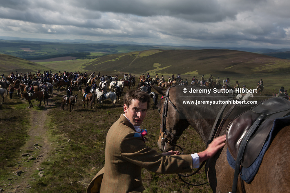 Horsemen, led by  Royal Burgh Standard Bearer Martin Rodgerson and his Burleymen attendants, arrive at the Three Brethren cairns summit, to check the boundaries of the lands, during the Common Riding festivities in Selkirk, in Selkirk, Scotland, Friday 14th June 2013. <br /> N55&deg;34.657'<br /> W2&deg;54.081'