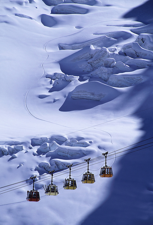 Travel. Editorial. View of La Grave glacier and gondola with single snowboard track in the background.