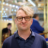 Garden City, New York, USA. March 9, 2019.  Artist MICHAEL WHITE poses in front of Nunley's Carousel during Unveiling Ceremony of his mural of close-up of Nunley's Carousel lead horse. Event was held at historic Nunley's Carousel in its Pavilion on Museum Row on Long Island. After speeches by elected officials and members of Baldwin Civic Association and Baldwin Historical Society, and others, people enjoy free carousel rides and food.
