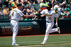 OAKLAND, CA - JULY 28:  Marcus Semien #10 of the Oakland Athletics is congratulated by third base coach Matt Williams #4 after hitting a home run against the Texas Rangers during the third inning at the RingCentral Coliseum on July 28, 2019 in Oakland, California. (Photo by Jason O. Watson/Getty Images) *** Local Caption *** Marcus Semien