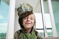 Portrait of smiling boy in dinosaur costume at home
