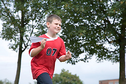 Boy running along flying a paper Airplane,