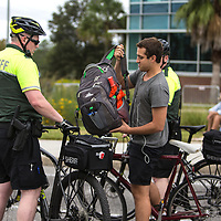 Campus police stop a student who ride down the street with a backpack which is one of the prohibited items for the Richard Spencer speech at the Phillips Center for the Performing Arts on the University of Florida campus in Gainesville, Florida on Thursday, October 18, 2017. (Alex Menendez)