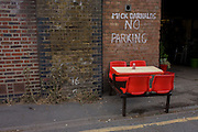 Red seating outside a burger bar under railway arches in the south London borough of Lambeth.