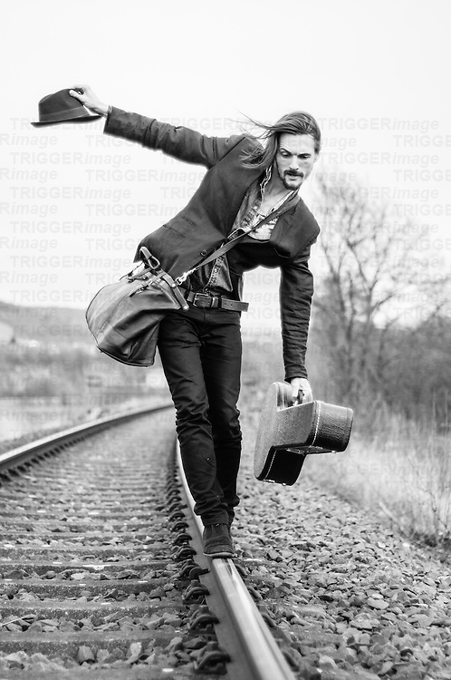 man leaving the town blancing on a railway with a guitar in one hand and his hat in the other hand