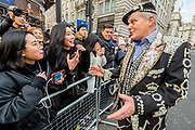A pearly king tries to chat to asian tourists - The New Years Day parade passes through central London.
