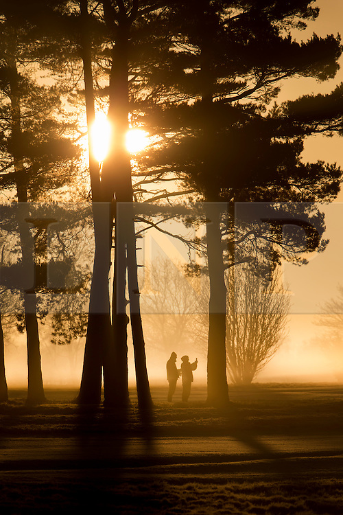 © Licensed to London News Pictures. 16/02/2016. Walton Heath, UK. Walkers stop to take a photograph at sunrise near Walton Heath golf course.  Temperatures locally were as low as -5 centigrade. Photo credit: Peter Macdiarmid/LNP