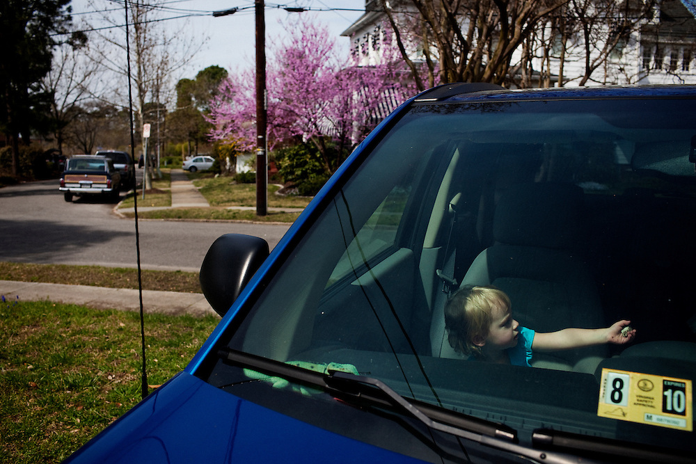 Madelyn Avery Eich, 2, plays while sitting in the passenger seat of her mother's car in the driveway of their home in Norfolk, Virginia on Saturday, April 3, 2010.