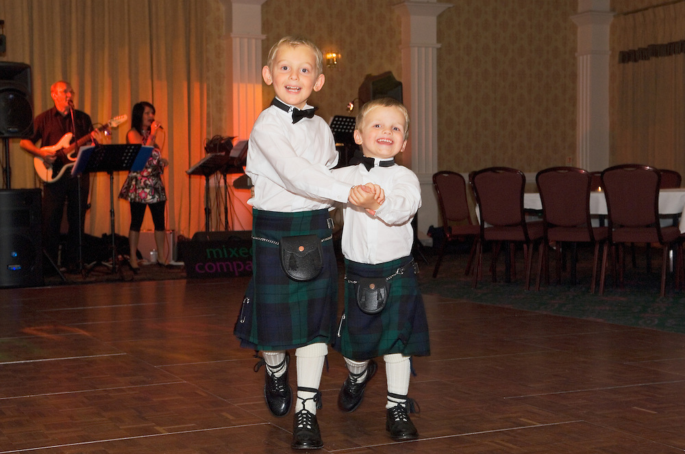 Two young boys in traditional Scottish costume of kilts, brogues, sporrans dancing at Scottish wedding reception party.