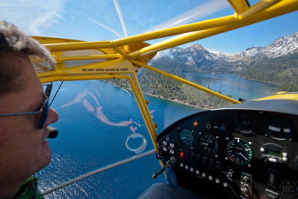 """Pilot Over Lake Tahoe 3"" - This pilot was photographed flying an amphibious seaplane over Lake Tahoe, CA. Emerald Bay can be seen in the distance."