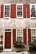 Flowers blooming in window boxes with traditional shutters along Queen Street in historic Charleston, SC.