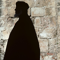 Israel, Jerusalem, Silhouette of Greek Orthodox priest outside Church of Holy Sepulcher on Palm Sunday