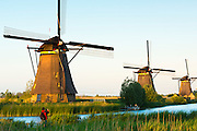 Man taking photograph of windmills at Kinderdijk UNESCO World Heritage Site, polder and dyke, Holland, The Netherlands