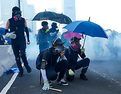 Hong Kong. 1 October 2019. After a peaceful march through Hong Kong Island by an estimated 100,000 pro democracy supporters, violent flared up at Tamar, Admiralty and moved through Wanchai district. Police used teargas,baton rounds and water cannon. Hard core group lit fires, threw bricks and Molotov cocktails at police. Violence continues into evening. Protestors shelter form teargas.  Iain Masterton/Alamy Live News.