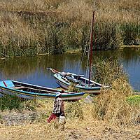 South America, Bolivia, Kala Uta Island. Aymara woman and boats on Kala Uta Island of Lake Titicaca.