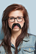 Portrait of young woman wearing eyeglasses and fake mustache against light blue background