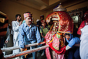 People carrying the palinquin of their deity through the entry gate of Raghunath Temple, Kullu. Kullu Dussehra is the Dussehra festival observed in the month of October in Himachal Pradesh state in northern India. It is celebrated in the Dhalpur maidan in the Kullu valley. Dussehra at Kullu commences on the tenth day of the rising moon, i.e. on 'Vijay Dashmi' day itself and continues for seven days. Its history dates back to the 17th century when local King Jagat Singh installed an idol of Raghunath on his throne as a mark of penance. After this, god Raghunath was declared as the ruling deity of the Valley.