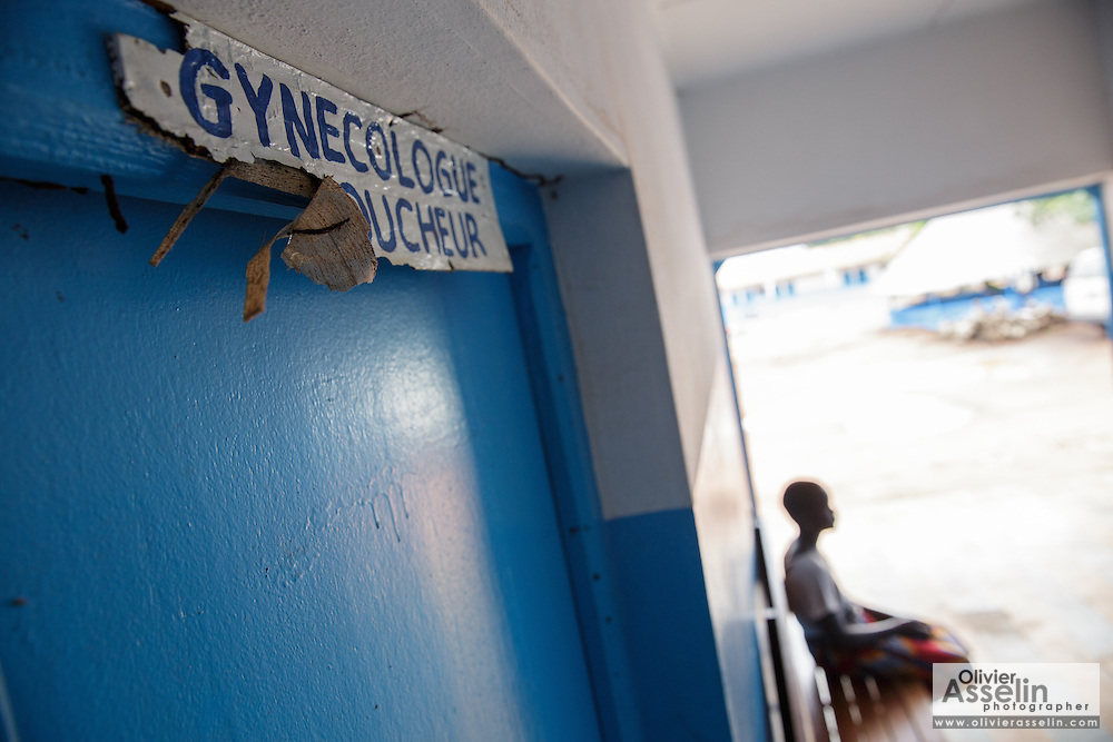 A teenage girl sits on a bench outside a gynecologist's office at the hospital in Katiola, Cote d'Ivoire on Saturday July 13, 2013.