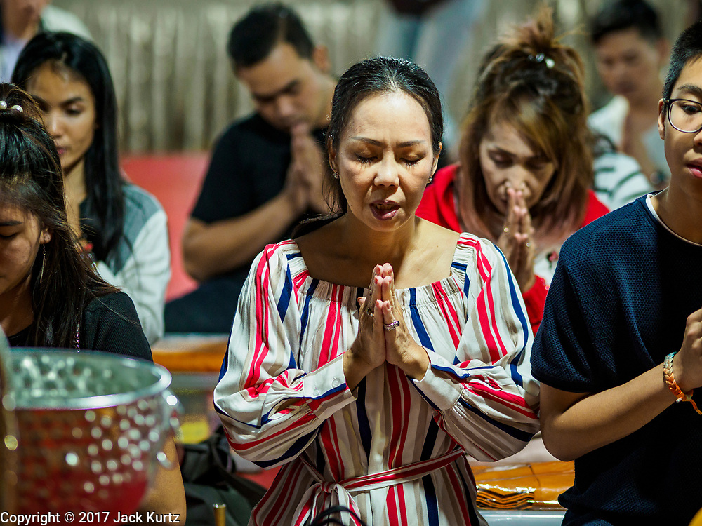 31 DECEMBER 2017 - BANGKOK, THAILAND:  A woman participates in an overnight meditation session on New Year's Eve at Wat Pathum Wanaram in central Bangkok. Many Thais go to temples and shrines to pray and meditate during New Year's Eve and New Year's Day.   PHOTO BY JACK KURTZ