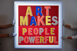 "© Licensed to London News Pictures. 26/02/2020. LONDON, UK. Technicians present ""Art Makes People Powerful"", 2019, by Bob and Roberta Smith (Starting price GBP4,000).  Preview of ""Human Touch"", an exhibition of one-of-a-kind artworks by international contemporary artists in collaborations with stitchers in British prisons.  In association with the charity Fine Cell Work, the artworks are on show at Sotheby's New Bond Street 26 February to 3 March 2020.  Photo credit: Stephen Chung/LNP"