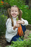 Girl (5-6) holding carrots in garden
