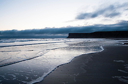 © Licensed to London News Pictures. 10/03/2014<br /> <br /> Saltburn, Cleveland, United Kingdom<br /> <br /> Waves roll gently over the beach as clouds sit over Huntcliff at first light in Saltburn by the Sea in Cleveland.<br /> <br /> Photo credit : Ian Forsyth/LNP