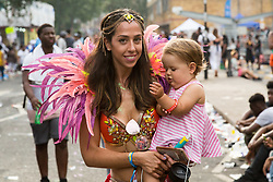London, August 28 2017. A woman carries a toddler as the procession winds down on Day Two of the Notting Hill Carnival, Europe's biggest street party held over two days of the August bank holiday weekend, attracting over a million people. © Paul Davey.
