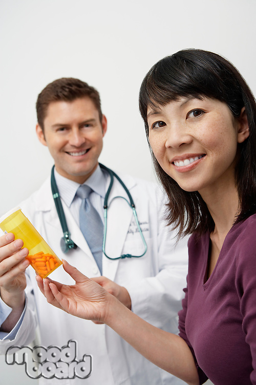 Doctor giving female patient medication in hospital
