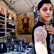 A young Copt boy proudly shows his tattoo outside the church in Cairo