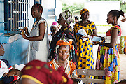 Rita Sahi, 25, who is 7-month pregnant with her third child, waits in line to pick up her prescription from the pharmacy counter of the Libreville health center in Man, Cote d'Ivoire on Wednesday July 24, 2013.