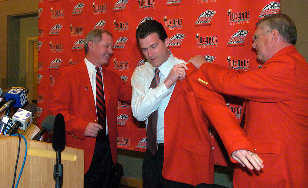 03-22-07 / JIM THOMPSON/UNM's president David J. Schmidly (right ) and Athletic Director Paul Krebs help the new UNM basketball coach into his new Lobo red jacket.