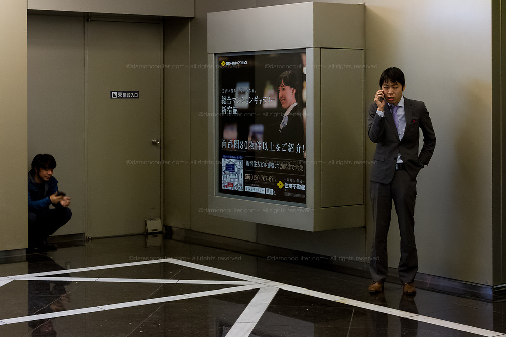 Two salarymen using mobile telephones inside the NS Building in Shinjuku, Tokyo, Japan Friday February 23rd 2018