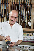 Portrait of a mature merchant with credit card reader in gun shop