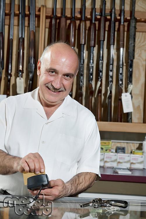 Portrait of a mature merchant with credit card reader in gun shop