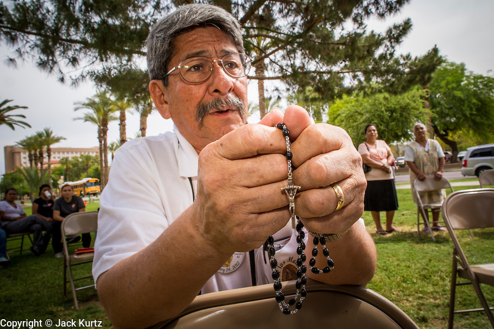 25 APRIL 2012 - PHOENIX, AZ: STEVE LOPEZ, from Glendale, AZ, prays the rosary during a vigil against SB1070 at the Arizona State Capitol Wednesday. Immigrants' rights groups opposed to SB1070 and Tea Party affiliated groups that support SB1070 gathered at the state capitol in Phoenix Wednesday to express their opposition and support of the bill. SB1070 was signed by Arizona Governor Jan Brewer in April 2010. At the time it was the toughest anti-illegal immigration bill in the country. Immigrants' rights groups sued Arizona and the federal courts stopped enforcement of the bill. The bill ended up in the US Supreme Court which heard arguments Wednesday. A ruling on the bill is expected in June.    PHOTO BY JACK KURTZ