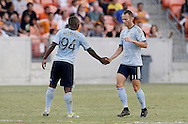 Jun 29, 2016; Houston, TX, USA; Sporting Kansas City midfielder Jimmy Medranda (94) celebrates midfielder Brad Davis (11) goal against the Houston Dynamo in the second half at BBVA Compass Stadium. Dynamo won 3 to 1. Mandatory Credit: Thomas B. Shea-USA TODAY Sports