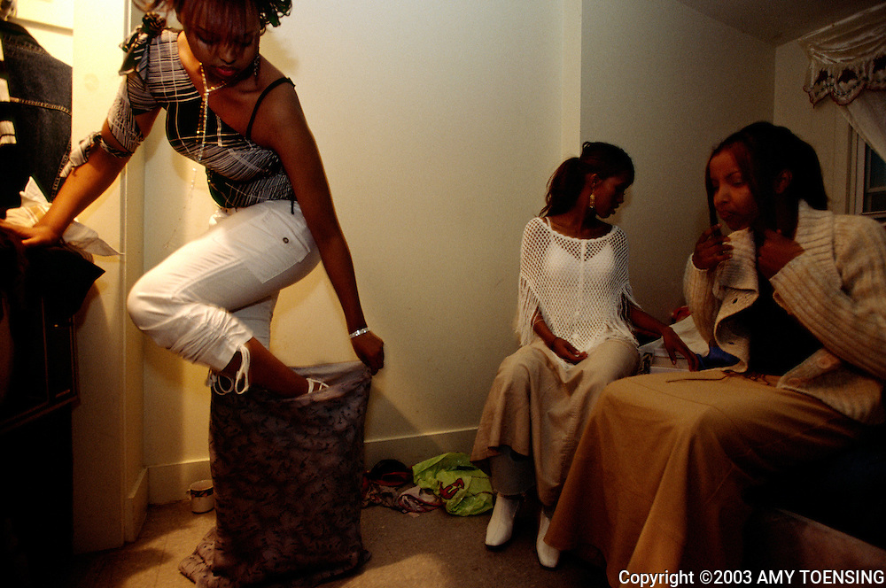 PORTLAND, ME - APRIL 18: A group of Somali teenage girls cover their short skirts and tight jeans with long skirts in order to sneak out of their homes and attend an alcohol-free dance for minors at a dance club April 18, 2004 in Portland, Maine. Going to a dance dressed in western clothes and dancing with boys is strictly forbidden in many of the Muslim families in Maine. Muslim females in the United States straddle two cultures, as they are expected to uphold many of the customs and traditions of Islam in the face of western culture. (Photo by Amy Toensing). _________________________________<br /> <br /> For stock or print inquires, please email us at studio@moyer-toensing.com.