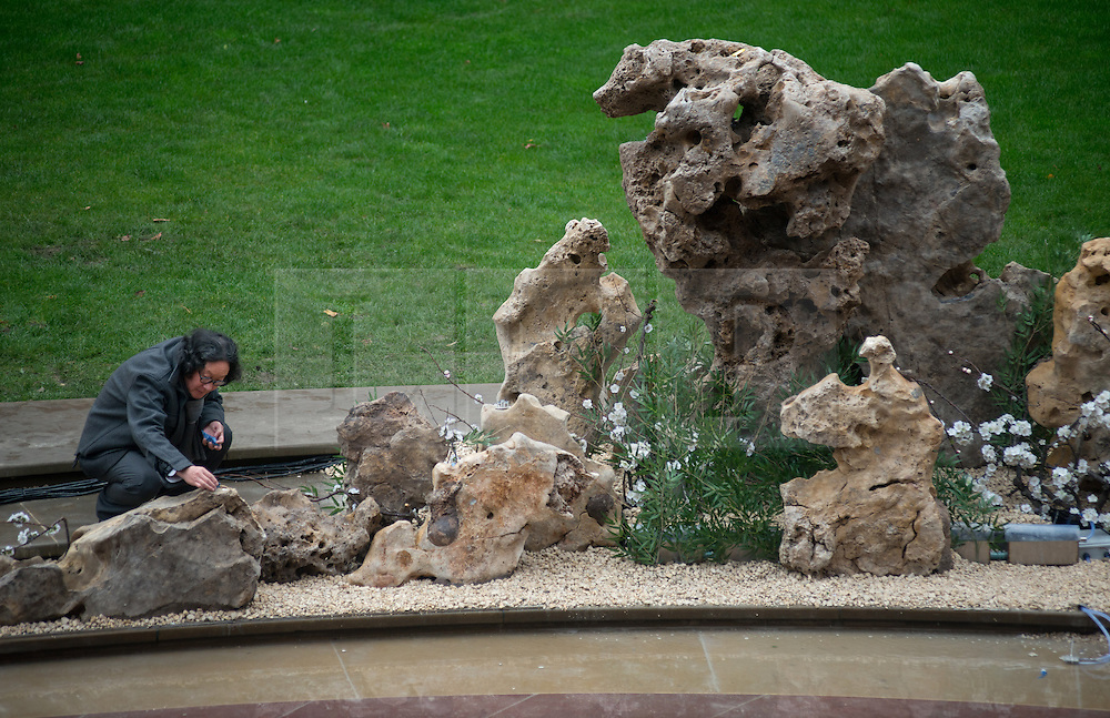 © Licensed to London News Pictures.31/10/2013. London, UK. Xu Bing, Chines artist crouches by the lake of he John Madejski Garden at V&A Museum, where his new installation is shown. Travelling to the Wonderland inspired by the classic Chinese fable Tao Hua Yuan (The Peach Blossom Spring). The V&A invited Xu Bing to create a major new work to coincide with the Museum's forthcoming exhibition, Masterpieces of Chinese Painting 700 – 1900.Photo credit : Peter Kollanyi/LNP