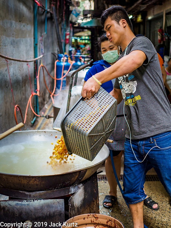 03 FEBRUARY 2019 - BANGKOK, THAILAND: A man dumps soybeans into a cooking vat in Bangkok's Chinatown. The soybeans will be used to make desserts and snacks for Chinese New Year. Chinese New Year celebrations in Bangkok start on February 4, 2019. The coming year will be the Year of the Pig in the Chinese zodiac. About 14% of Thais are of Chinese ancestry and Lunar New Year, also called Chinese New Year or Tet is widely celebrated in Chinese communities in Thailand.         PHOTO BY JACK KURTZ
