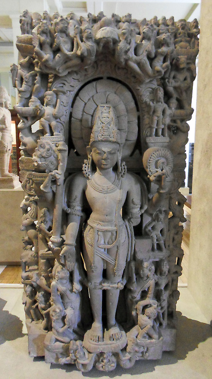 Sandstone stele with a figure of Vishnu From central India, 10th century AD. Vishnu is the preserver and maintainer of spiritual, moral and temporal order in the Hindu trinity. His character is almost like a monarch, which explains his tall crown, elaborate jewellery and upright posture. In his hands he holds a chakra (wheel) and gada (mace). His third hand is held in varadamudra (the gesture of giving), and his fourth hand, now broken, would probably have held a conch. Vishnu is also commonly seen holding a lotus, alluded to here by the small floral motif on his open right palm. This stele is typical of the sculptures from niches in tenth-century temple walls in central India.